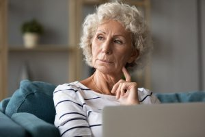 Woman in front of laptop wondering if worry-free senior living is still possible