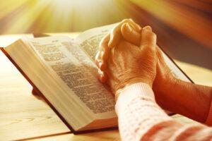 An adult's praying hands on an open Bible